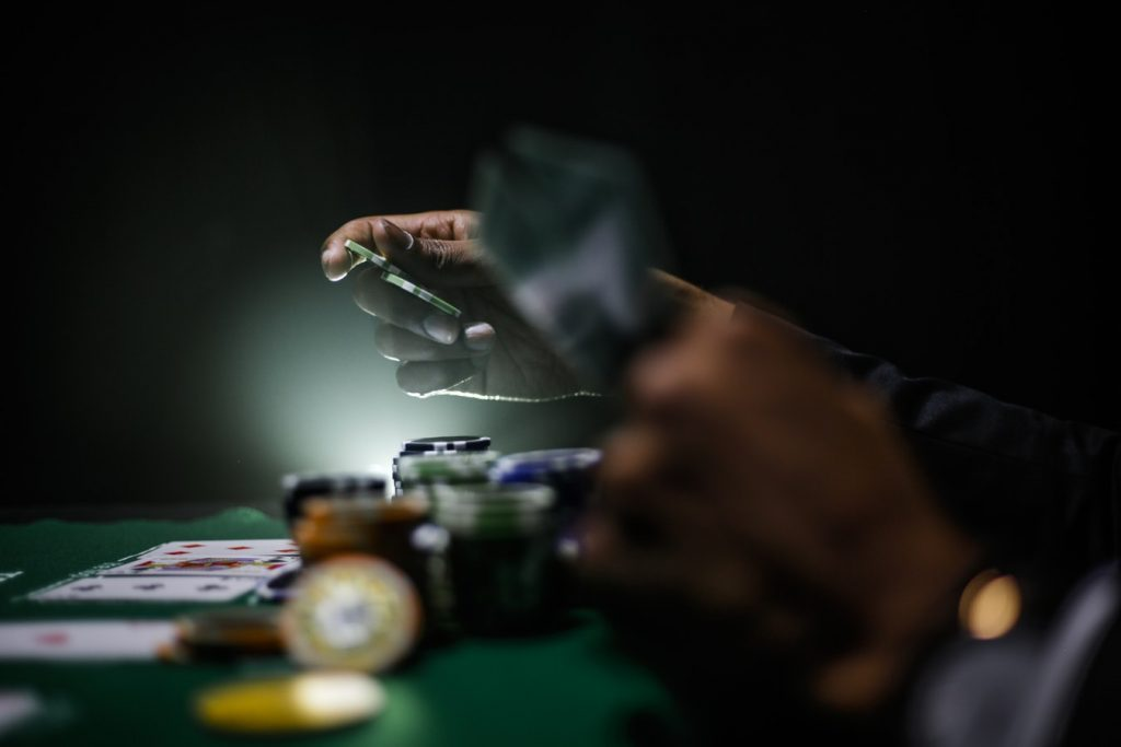 Primer plano de unas manos jugando al póker con fichas y cartas sobre un tapete verde y un fondo oscuro